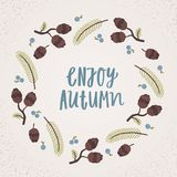 Enjoy autumn lettering. Cones, berries and branches wreath. royalty free illustration