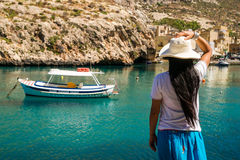 Enjoy the bay. An asian lady enjoys the view over the waters of Xlendi Bay at Gozo Island, part of the maltese archipel Royalty Free Stock Photo