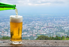 Enjoy beer with urban cityscape. Royalty Free Stock Image
