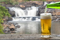 Enjoy beer with waterfall landscape. Royalty Free Stock Photography