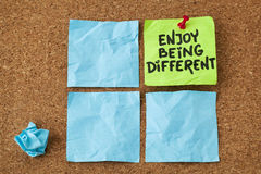 Enjoy being different. Advice - lifestyle or nonconformist concept - handwriting on colorful sticky notes Stock Images