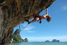 Enjoy climbing!. Adult climbing hard overhanging wall in Krabi, Thailand royalty free stock images