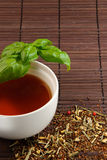 Enjoy a cup of tea. Calming tea with tea leaves on a bamboo mat Royalty Free Stock Image