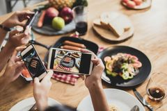 Enjoy dinner eating party and celebration with friends and taking photo by phone to post into social network, top view of food on. Table and group of funny and royalty free stock images