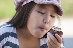 Enjoy eating. Cute asian girls enjoy eating chocolate cupcake stock photo