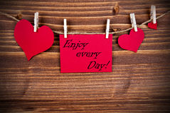 Enjoy Every Day on a red Label. The Saying Enjoy every Day on a red Label with Hearts Hanging on a Line on a Wooden Background Royalty Free Stock Photo