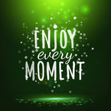 Enjoy every moment drawing lettering at green backdrop Stock Photography