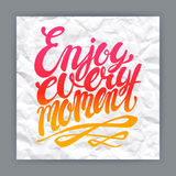 Enjoy every moment. Hand-drawn quote on crumpled paper background Royalty Free Stock Images