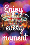 ENJOY EVERY MOMENT. Inspirational Typographic Quote. Merry-Go-Round illuminated at night with colorful bokeh. Stock Photo