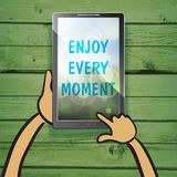Enjoy every moment on the screen of multimedia tablet with natur. Al wooden background. Typography on beautiful colorful background with bokeh Stock Photo
