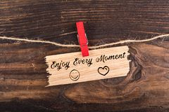 Enjoy every moment. Write in break wood with clothes pin and rope on wood stock photo