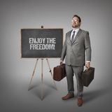 Enjoy the freedom text on blackboard with businessman Stock Images