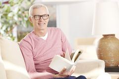 Enjoy a good book. Shot of an older man relaxing at home and reading a book Royalty Free Stock Photography