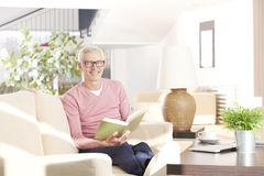 Enjoy a good book. Shot of an older man relaxing at home and reading a book Royalty Free Stock Photo