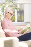 Enjoy a good book. Shot of an older man relaxing at home and reading a book Stock Image