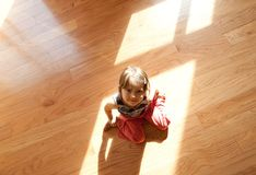 Enjoy hardwood floor. Little girl sitting on hardwood floor Stock Images