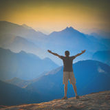 Enjoy the high peaks valley. Instagram stylisation. Man with raised hands standing on a mountain hill and welcome sunrise above the mountains. Instagram Stock Photography