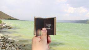 Enjoy the journey - travel and vacation concept. Inscription on the book and the sea stock footage