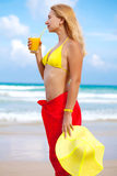 Enjoy juice. Woman enjoy juice on the tropical beach Royalty Free Stock Images