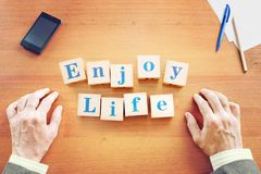 Enjoy life. Businessman made text from wooden cubes royalty free stock photo