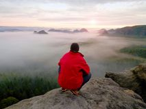 Enjoy life. Man in black trousers, jacket and dark cap sit on cliff`s edge and looking to landscape Stock Photos