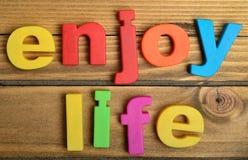 Enjoy life word. On wooden table Stock Photos