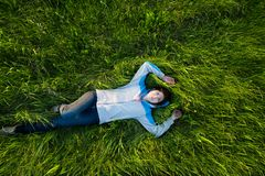 Enjoy life when you lay on the grass. Young and happy woman enjoy life. She is lay on the field with green grass. She smile and look up at the sky Stock Photography