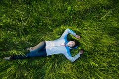 Enjoy life when you lay on the grass. Young and happy woman enjoy life. She is lay on the field with green grass. She smile and look up at the sky Royalty Free Stock Photos