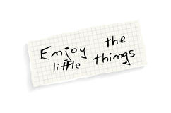 Enjoy the little things. Hand writing text on a piece of math paper isolated on a white background Stock Photography