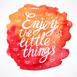 Enjoy the little things. Hand-drawn quote on watercolor background Stock Photo