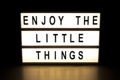 Enjoy the little things light box sign board. On wooden table royalty free illustration