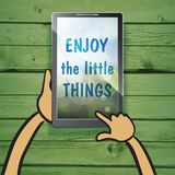 Enjoy the little things on the screen of multimedia tablet with. Natural wooden background. Typography on beautiful colorful background with bokeh Royalty Free Stock Images