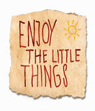 Enjoy the lttle things. An inspirational saying handwritten on a torn fragment of textured, grunge, paper with a sunburst in the corner - grab life with both Royalty Free Stock Images