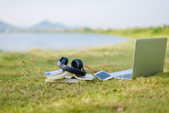 Enjoy lyssnande musik på gräsfältet av parkera royaltyfri foto