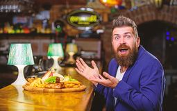 Enjoy meal. Cheat meal concept. Hipster hungry eat pub fried food. Restaurant client. Hipster formal suit sit at bar. Counter. Man received meal with fried stock photo