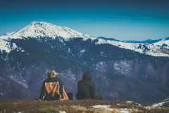 Enjoy the mountains covered by snow. Instagram stylization. Two hikers sit on a hill and enjoy the mountains covered by snow. Instagram stylization Royalty Free Stock Photos