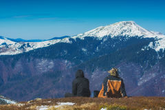 Enjoy the mountains covered by snow. Two hikers sit on a hill and enjoy the mountains covered by snow Royalty Free Stock Image
