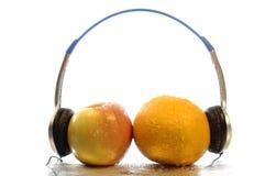 Enjoy music. Apple and orange with headphone stock photos
