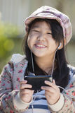 Enjoy music. Asian girl listening to music on her cell phone stock photo