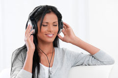 Enjoy the music and relax. Beautiful young woman enjoy the music with headphones at home Stock Photography