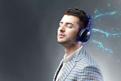 Enjoy the music. Young man with headphones enjoys listening to the magic of music Royalty Free Stock Image