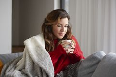 Enjoy my coffee at home on the sofa. Shot of a mature woman relaxing at home with a cup of coffee while sitting on sofa and she covers herself with a blanket Stock Image
