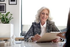 Charming gray-haired lady is expressing gladness. Enjoy my work. Cheerful gorgeous elegant business women is putting signature on important document with smile royalty free stock images