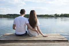 Enjoy the nature!. Young couple sits on the wooden mooring and enjoy the magic view Royalty Free Stock Image