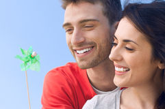 Enjoy the new energy. Happy smiling couple playing with a toy windmill outdoor, symbol of environmental conservation and renewable energy Stock Photography