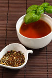 Enjoy peaceful time with a cup of tea. Cup of tea with basil leaves on a bamboo mat with tea leaves Stock Images