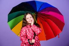 Enjoy rain concept. Kid girl happy hold colorful rainbow umbrella. Rainy weather with proper garments. Bright umbrella. Be rainbow in someones cloud. Rainy day royalty free stock image
