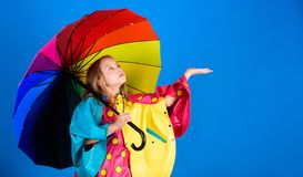 Enjoy rainy weather with proper garments. Waterproof accessories make rainy day cheerful and pleasant. Kid girl happy. Hold colorful umbrella wear waterproof stock image