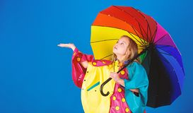 Enjoy rainy weather with proper garments. Waterproof accessories make rainy day cheerful and pleasant. Kid girl happy. Hold colorful umbrella wear waterproof royalty free stock photos