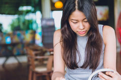 Enjoy relax times with reading book. Asian woman Thai teen serious focus to read pocket book in coffee shop in the morning vintage color tone Stock Photos